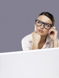 Portrait of a thoughtful business woman wearing spectacle with laptop against grey background
